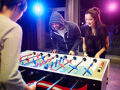 Happy friends playing foosball - p300m2079031 by Christian Vorhofer