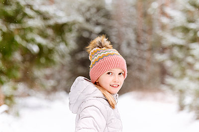 Smiling girl wearing warm clothing standing in forest during winter - p300m2251466 by Ekaterina Yakunina