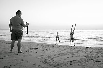 Father taking picture of children on beach - p312m1211254 by Johan Willner