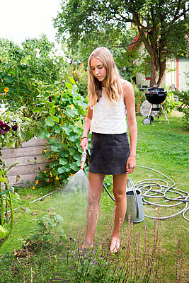 Girl working in garden - p312m1532922 by Lena Granefelt