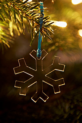 Transparent snowflake decoration hanging from Christmas tree in London home UK - p349m695298 by Jon Day