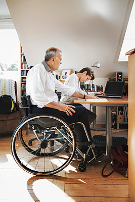 Side view of disabled man looking at son studying at home - p426m1062524f by Maskot