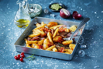 Roasted vegetables with red onions in roasting tin, seasonal christmas food - p429m2068531 by Danielle Wood
