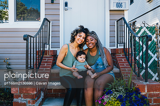 Portrait of smiling lesbians with cute baby boy sitting outside house - p1166m2130596 by Cavan Images