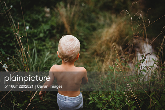 Back view of blonde child walking on hiking trail among green plants - p1166m2292821 by Cavan Images
