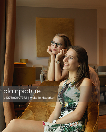 Female teenager and young woman in living room - p1376m2107372 by Melanie Haberkorn