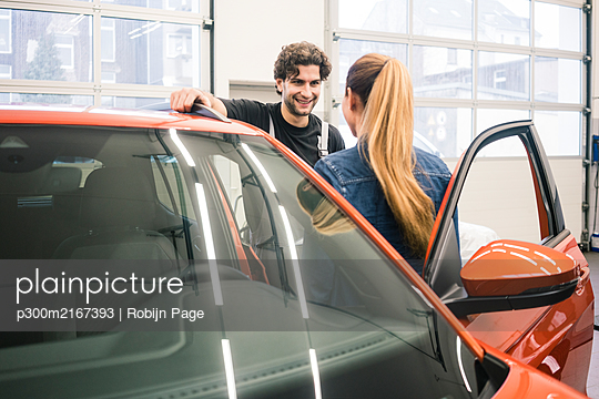 Car mechanic talking to client in workshop - p300m2167393 by Robijn Page