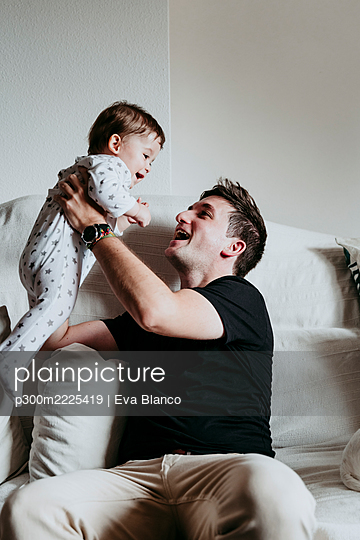 Cheerful father picking up son while sitting on sofa at home - p300m2225419 by Eva Blanco