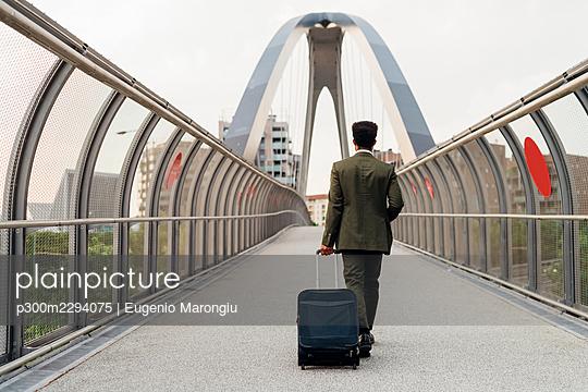 Businessman walking with wheeled luggage on bridge - p300m2294075 by Eugenio Marongiu