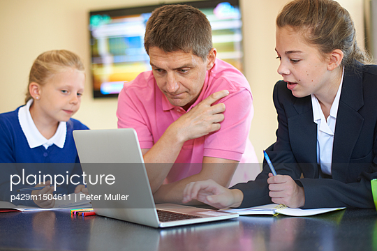 Father helping daughters with homework at kitchen counter - p429m1504611 by Peter Muller