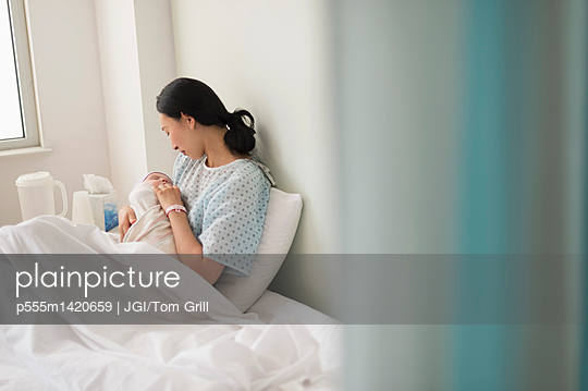 Asian mother holding newborn baby in hospital - p555m1420659 by JGI/Tom Grill
