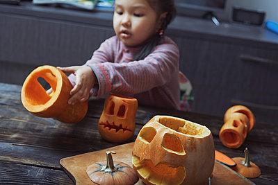 Girl carving Halloween pumpkins - p1023m1584027 by Arman Zhenikeyev