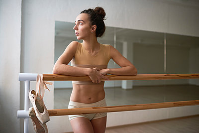 Thoughtful woman looking away while leaning on barres at dance studio - p1166m1555677 by Cavan Images