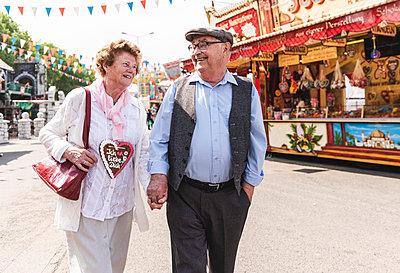 Happy senior couple walking hand in hand on fair - p300m1588062 von Uwe Umstätter