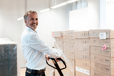 Smiling senior businessman holding pallet jack in warehouse - p300m2265757 by Gustafsson