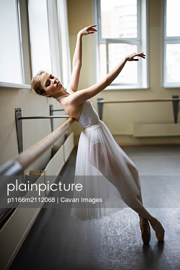 Side view of confident ballet dancer practicing by railing in studio - p1166m2112068 by Cavan Images