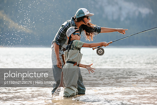 Mother and son fly fishing in sunny lake - p1192m2129176 by Hero Images