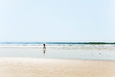 Man riding bicycle at shore on beach against clear sky - p1166m1210083 by Cavan Images