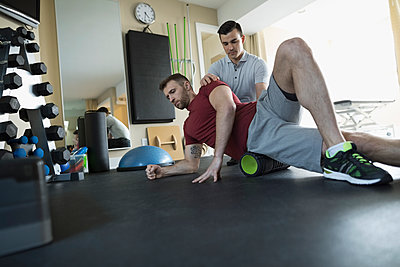 Male physiotherapist guiding client stretching in clinic gym - p1192m1447351 by Hero Images