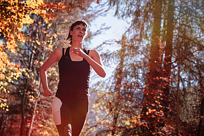 Woman jogging in autumn forest - p300m2166368 by Studio 27
