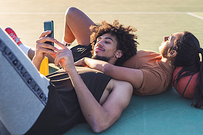 Sportive young couple taking a break lying on basketball court - p300m2171157 by Eugenio Marongiu