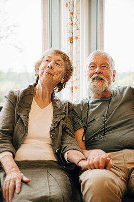 Senior couple holding hands while sitting against window at nursing home - p426m2149311 by Maskot