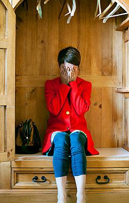 Woman crying in a wardrobe - p4320733 by mia takahara