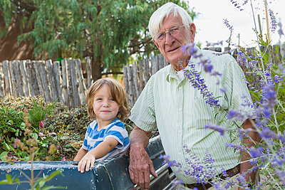 Portrait of smiling Caucasian grandfather and grandson at truck - p555m1301778 by Marc Romanelli