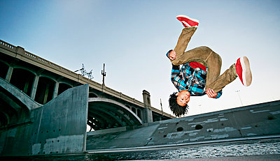 Asian man break dancing under overpass - p555m1454010 by Peathegee Inc
