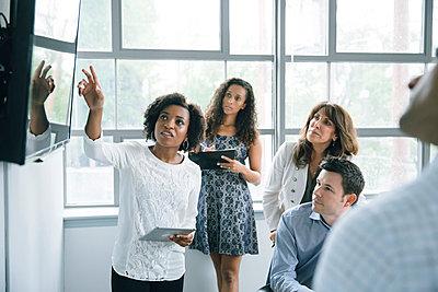 Businesswoman talking near visual screen in meeting - p555m1504107 by John Fedele