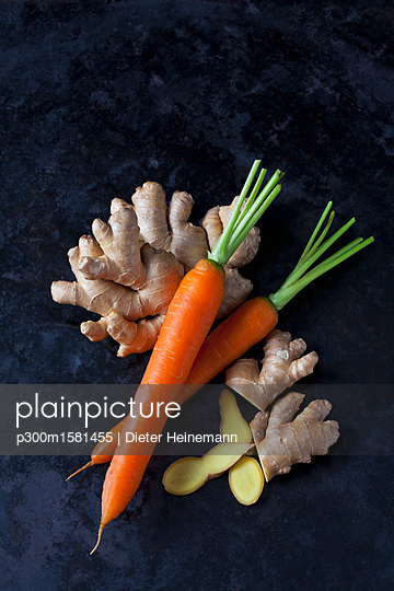 Fresh ginger and carrots on dark metal - p300m1581455 von Dieter Heinemann