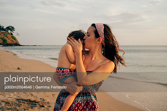 Thailand, Krabi, Koh Lanta, Mother with little daughter on her shoulders on the beach at sunset - p300m2004646 von Gemma Ferrando