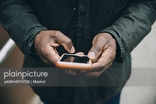 Midsection of businessman using smart phone while standing on footbridge in city - p426m2074726 by Maskot