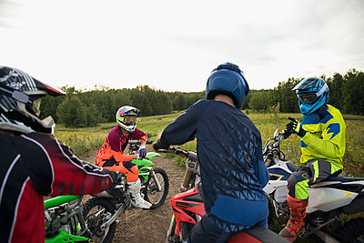 Male friends on motorbikes talking - p1192m1500159 by Hero Images
