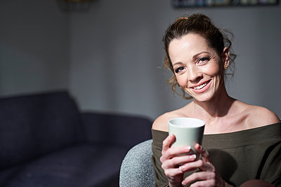 Portrait of smiling woman holding cup at home - p300m2114913 by Philipp Nemenz