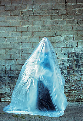 Woman standing fully covered under plastic sheet - p577m2038712 by Mihaela Ninic