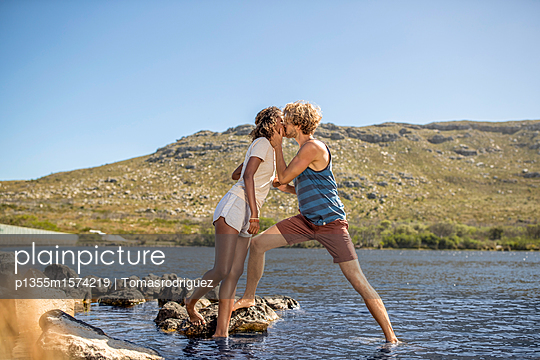 Junges Paar am Flussufer küsst sich - p1355m1574219 von Tomasrodriguez