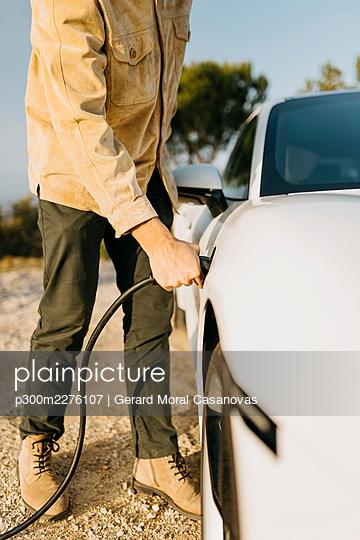 Man charging electric car during road trip - p300m2276107 by Gerard Moral Casanovas