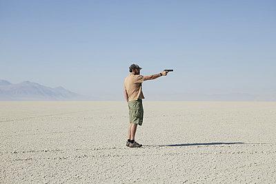 Man aiming hand gun, standing in vast, barren desert - p1100m876527f by Paul Edmondson