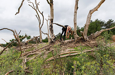 Woman hanging over a branch of a dead tree - p1231m2013900 by Iris Loonen