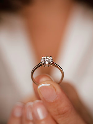 Woman's hand holding diamond ring - p1522m2071762 by Almag