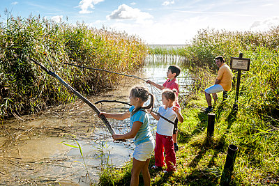 Children playing with wood sticks at water course, Darss, Mecklenburg-Western Pomerania, Germany - p300m2143561 by Ega Birk