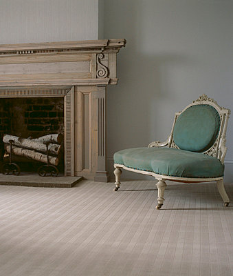 Neutral coloured carpeted living room with open fire and upholstered vintage style chair - p349m695203 by Emma Lee