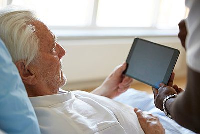 Cropped image of male nurse assisting senior man in using digital tablet at hospital - p426m1494053 by Maskot