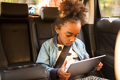 Girl using digital tablet while sitting in electric car - p426m2072433 by Maskot