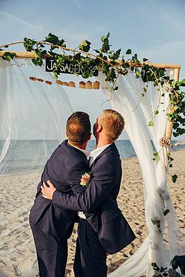 Schwules Brautpaar gibt sich Eheversprechen am Strand - p432m2142137 von mia takahara