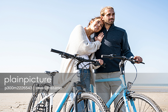 Smiling beautiful woman with head on boyfriend's shoulder standing with bicycles at beach against clear sky on sunny day - p300m2226543 by Uwe Umstätter
