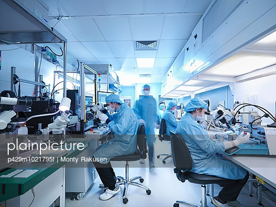 Electronics workers in clean room laboratory - p429m1021795f by Monty Rakusen