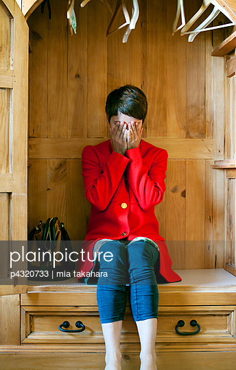 Woman crying in a wardrobe - p4320733 by mia takahara