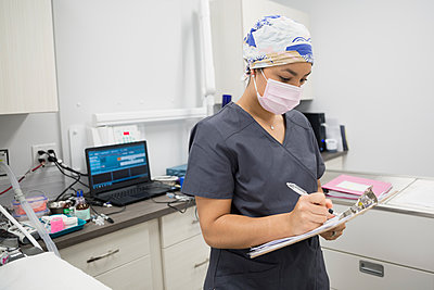 Veterinarian writing on clipboard in clinic examination room - p1192m1127928f by Hero Images